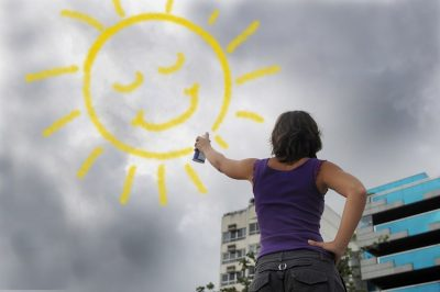 woman painting the sun onto the cloudy sky