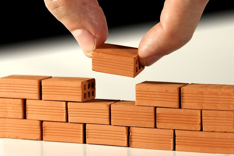 Large fingers building a tiny brick wall symbolizes using small investment ideas to cultivate wealth.