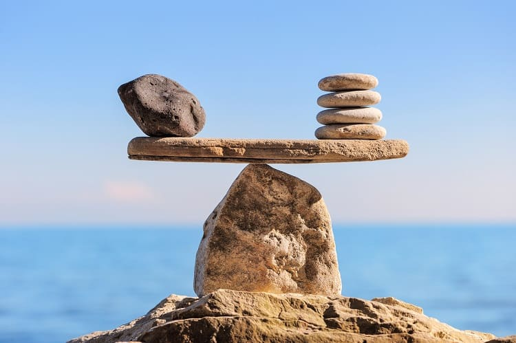 Rocks balanced on rocks. Growth stocks vs. dividend stocks.